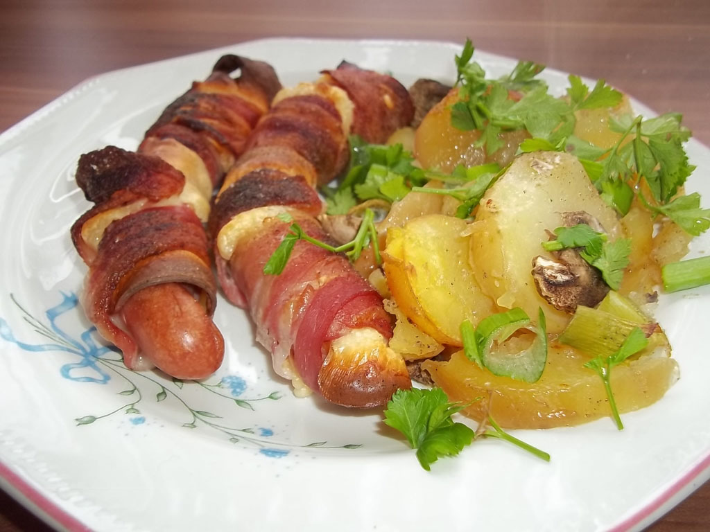Füstölt sajtba, baconbe tekert virsli krumpli-gombaágyon, csőben sütve